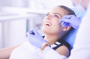 Young Female patient with open mouth examining dental inspection at dentist office