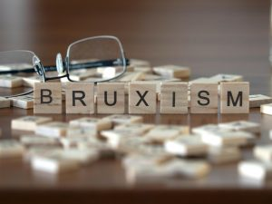 bruxism concept represented by wooden letter tiles on a wooden table with glasses and a book